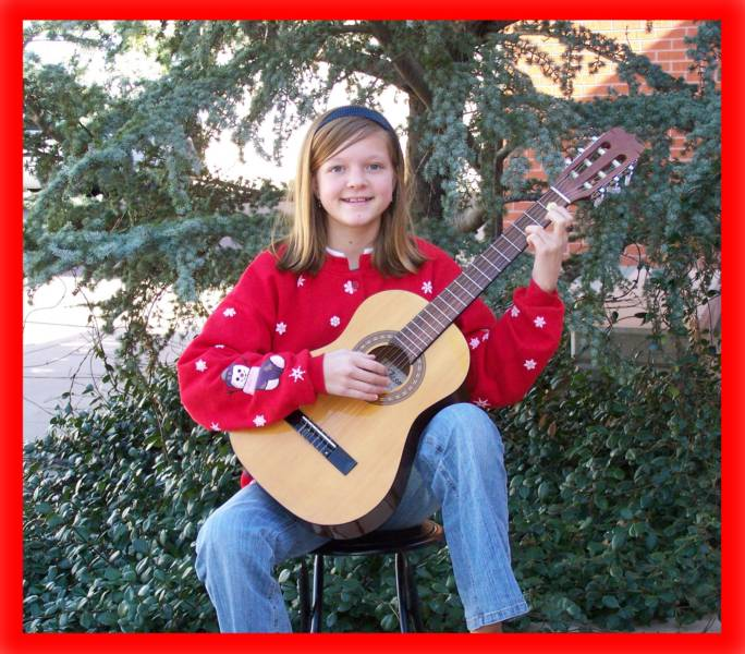 Young girl enjoying a classical guitar lesson